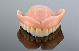 How Can Dental Implants Be Used to Improve My Full or Partial Dentures?